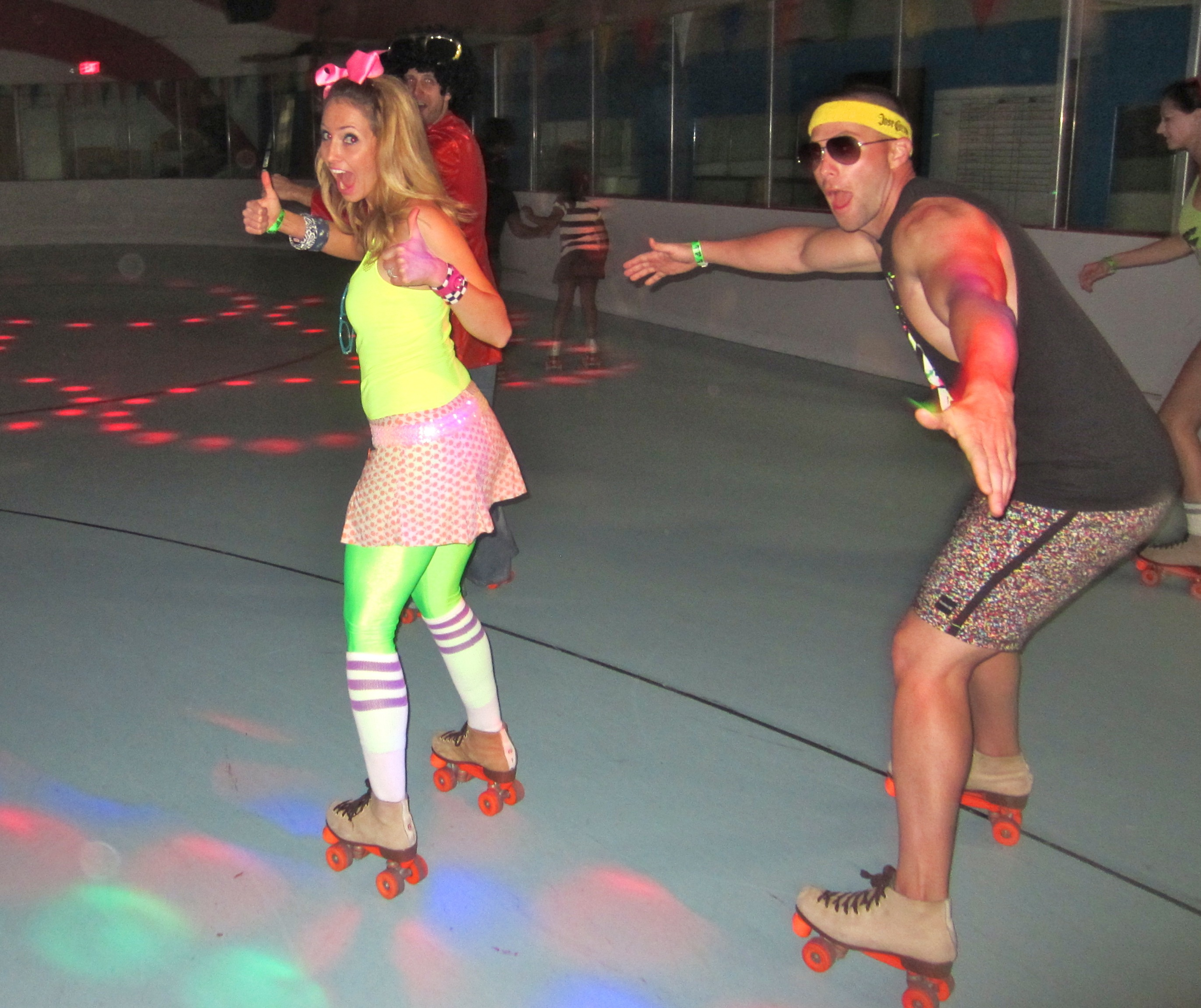 Adults roller skating in 80s gear